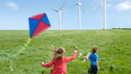 Children playing with kite and glider in front wind turbines.